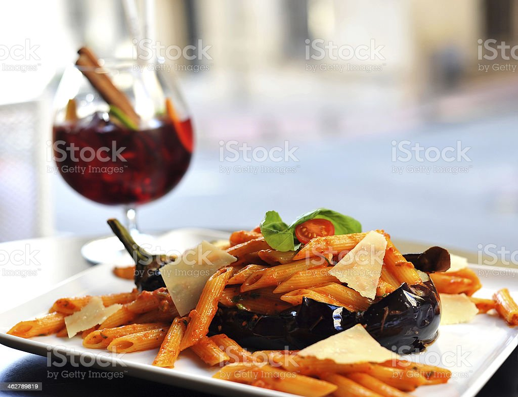 Eggplant pasta dish with a glass of red wine stock photo