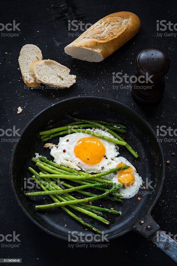 Eggs and asparagus in skillet stock photo