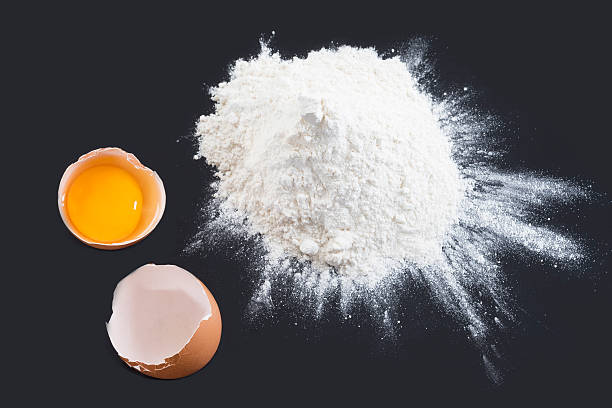 Eggs and flour on black background stock photo