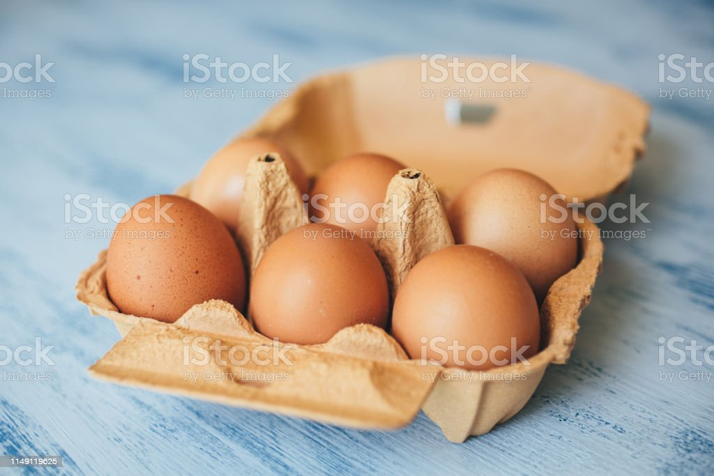Eggs background. Closeup view of chicken eggs in carton box on wooden...