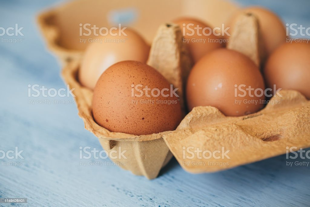 Eggs background. Closeup view of eggs in carton box on wooden table....