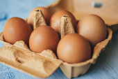Eggs background. Closeup view of eggs in carton box on wooden table. Food and health concept.