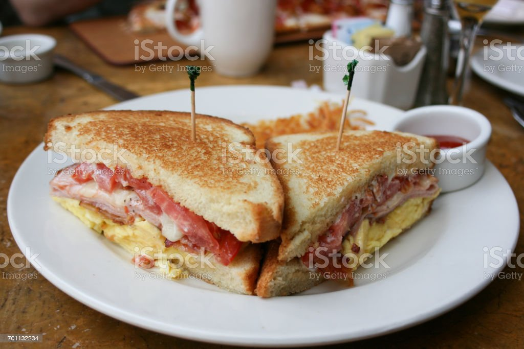 Eggs, bacon and cheese breakfast sandwich with hash brown potatoes stock photo