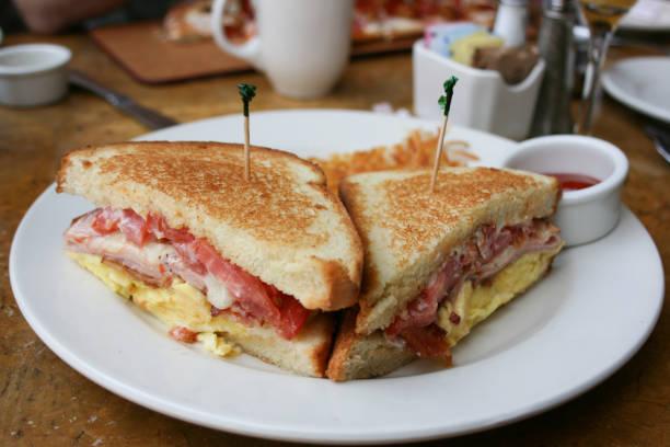 eiern, speck und käse frühstück sandwich mit hash brown kartoffeln - ei sandwiches stock-fotos und bilder
