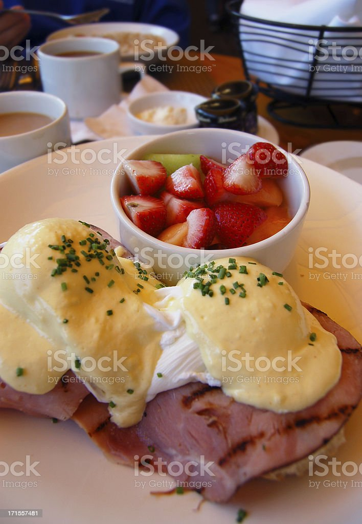 Eggs Benedict Breakfast with a Bowl of Fresh Fruit royalty-free stock photo