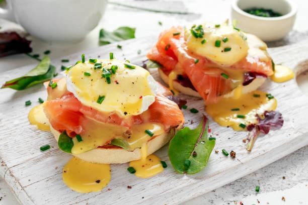 eier benedict auf englische muffins mit räucherlachs, salat-salat-mix und sauce hollandaise auf tafel - sauce hollandaise stock-fotos und bilder