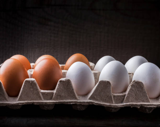 Eggs brown and white in paper box on dark background stock photo
