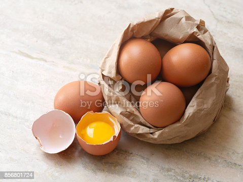 Eggs composition on marble surface, one of them is broken in two halves; some eggs are inside a paperbag. Natural day light horizontal composition with copy space, high angle view. No people. Color photography.