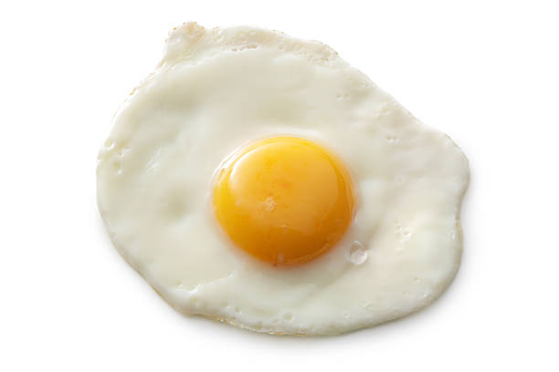eggs: fried egg isolated on white background - fried egg stock photos and pictures