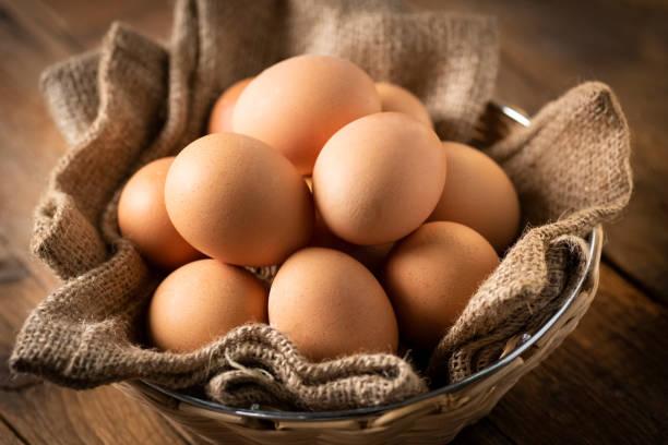 eggs in a basket on a wooden table - allevatore foto e immagini stock