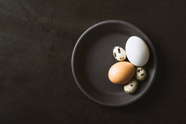Eggs in a bowl on black background stock photo