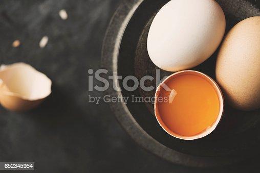 Fresh organic free range chicken eggs in black stone bowl on black rustic background. Top view shot.