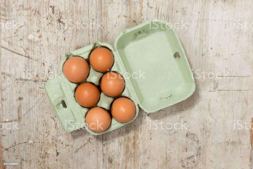Eggs in a Carton on a Wooden Surface stock photo