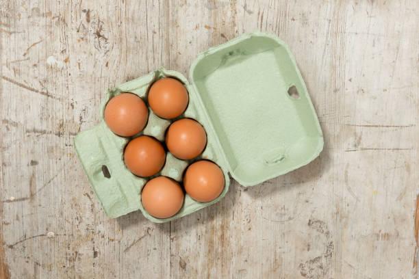 eiern in einem karton auf eine holzoberfläche - eierverpackung stock-fotos und bilder