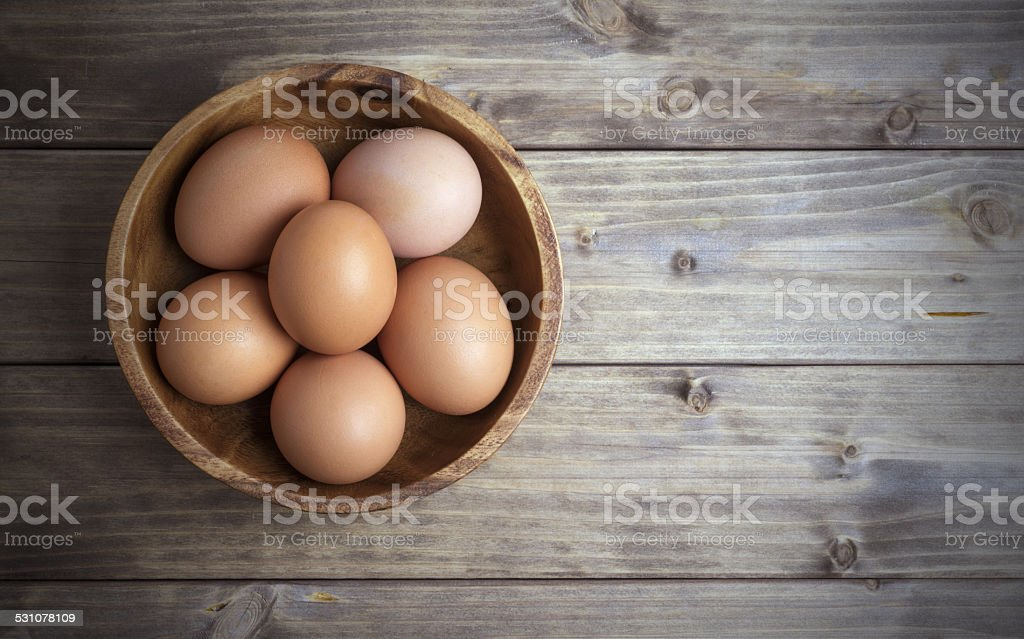 eggs in a wooden bowl stock photo
