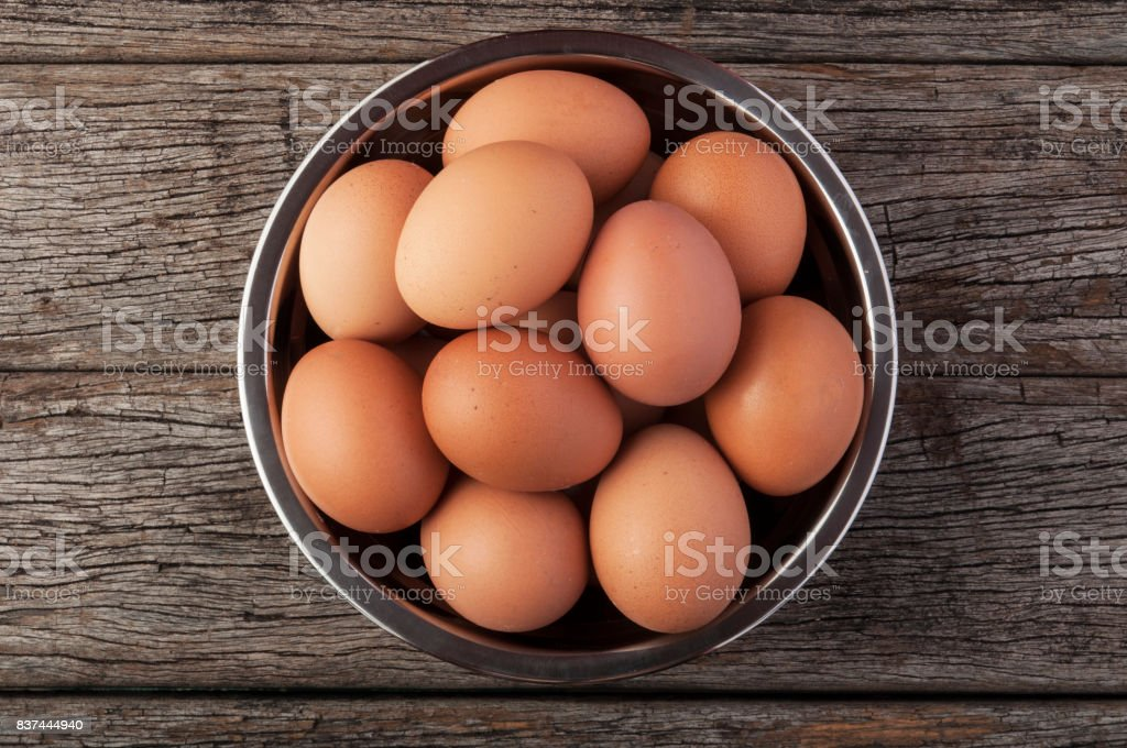 Eggs in bowl on wooden table background. stock photo