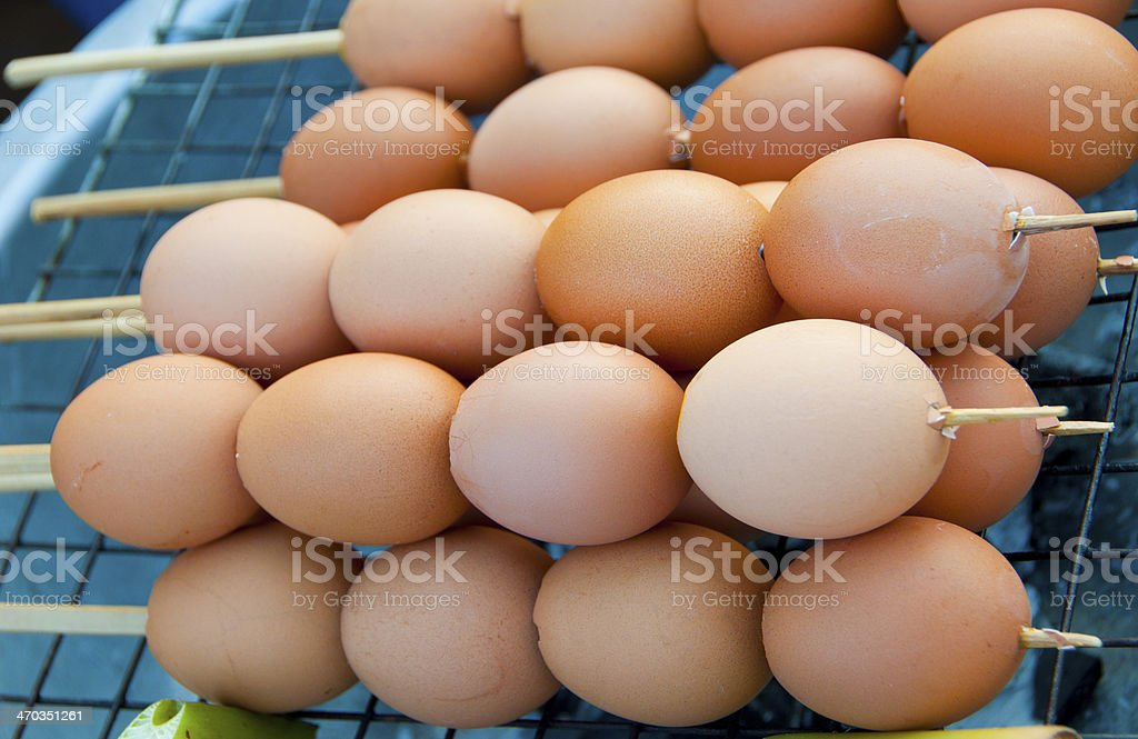 eggs in line by bamboo skewers and grilled stock photo