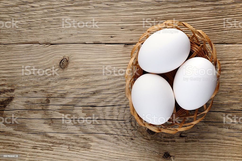 Eggs in small basket on wooden table stock photo
