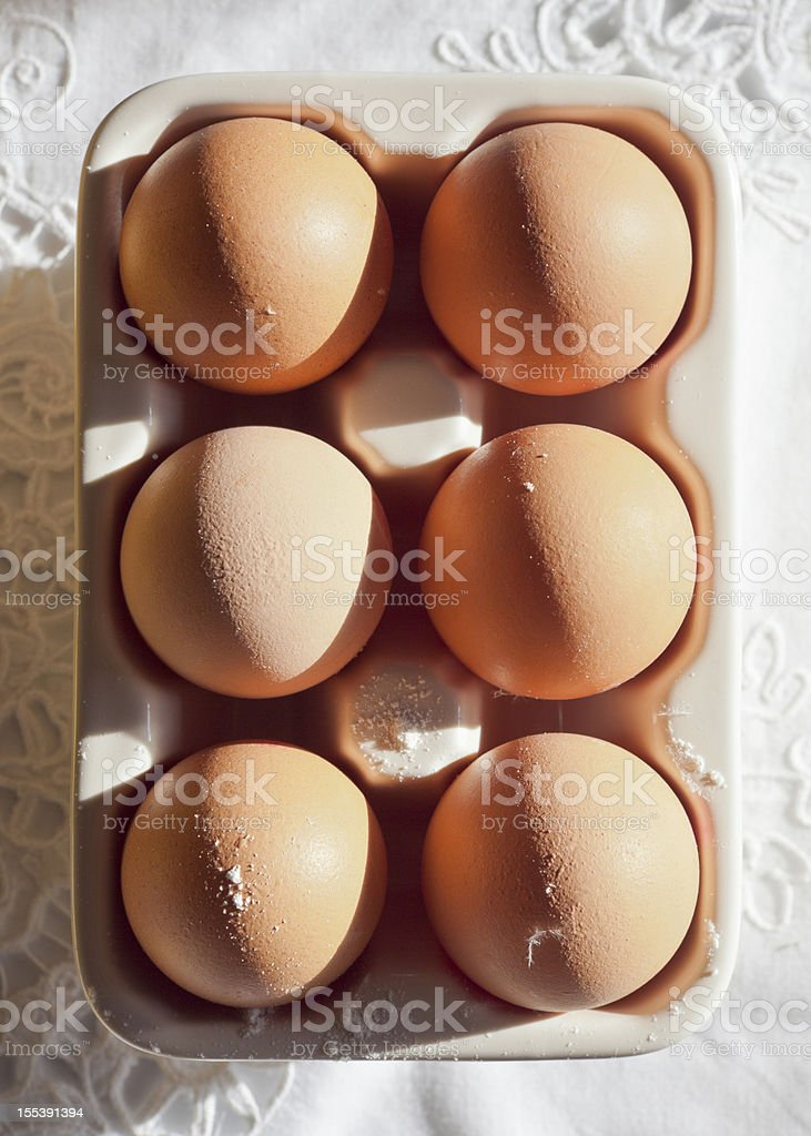 Eggs in strong natural sunlight with ceramic holder. stock photo