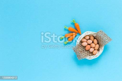 Eggs in the basket and carrots on blue paper texture background, healthy food concept, food handmade craft item