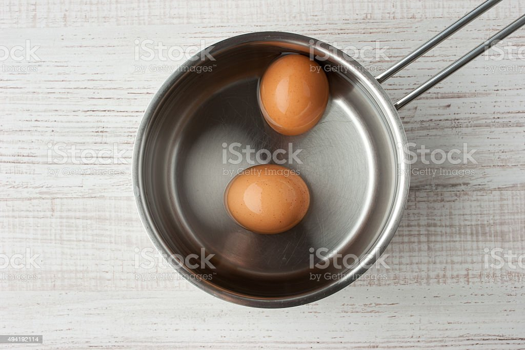 Eggs in water in a metal pan top view stock photo