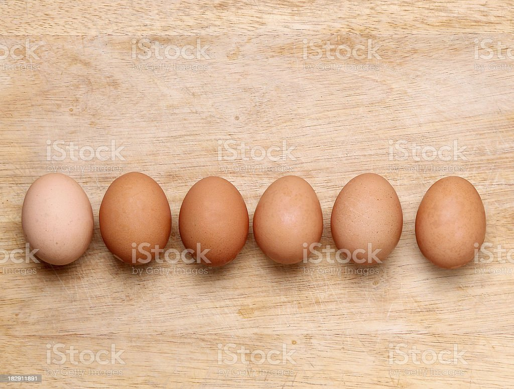 Eggs of different natural colors on wooden background stock photo