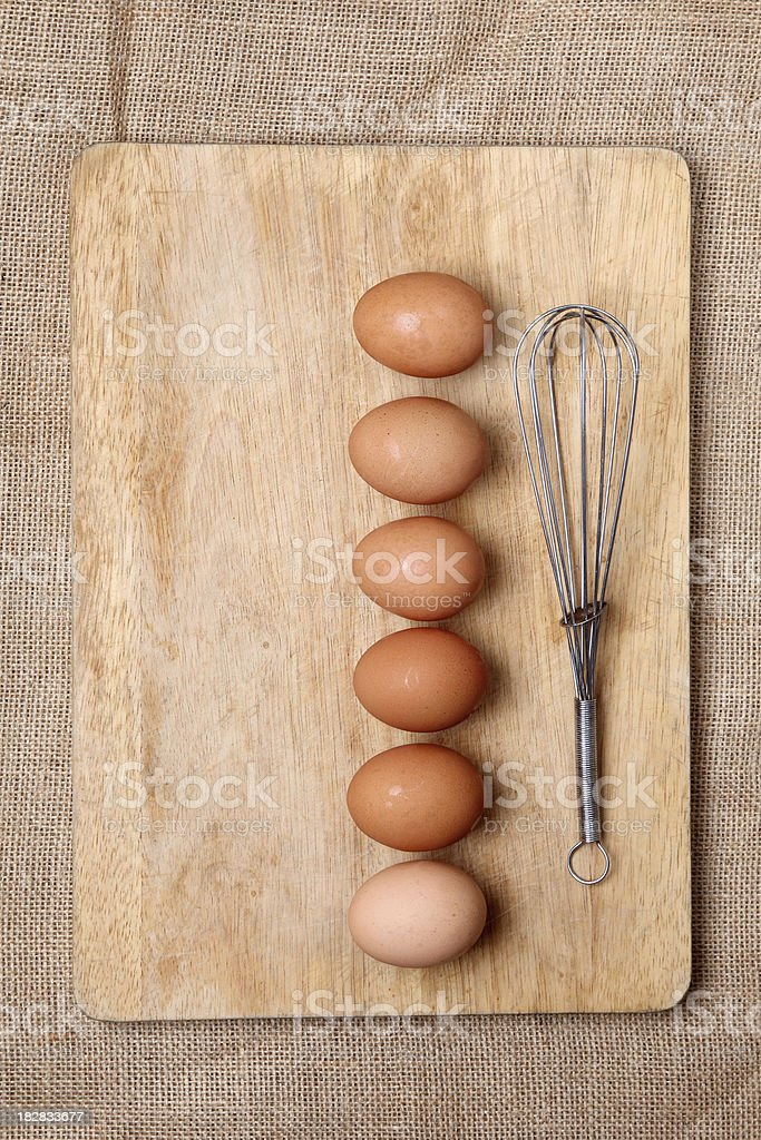 eggs on a cutting board with a whisk stock photo