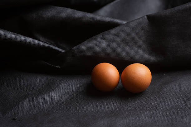 Cтоковое фото Eggs on black fabric background