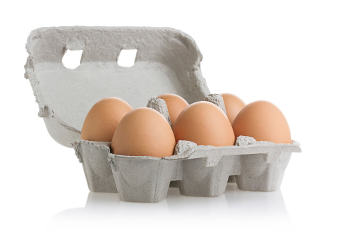 Six eggs in carton isolated on white with clipping path.