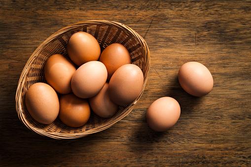 Fresh organic eggs in a wicker basket on rustic wood table