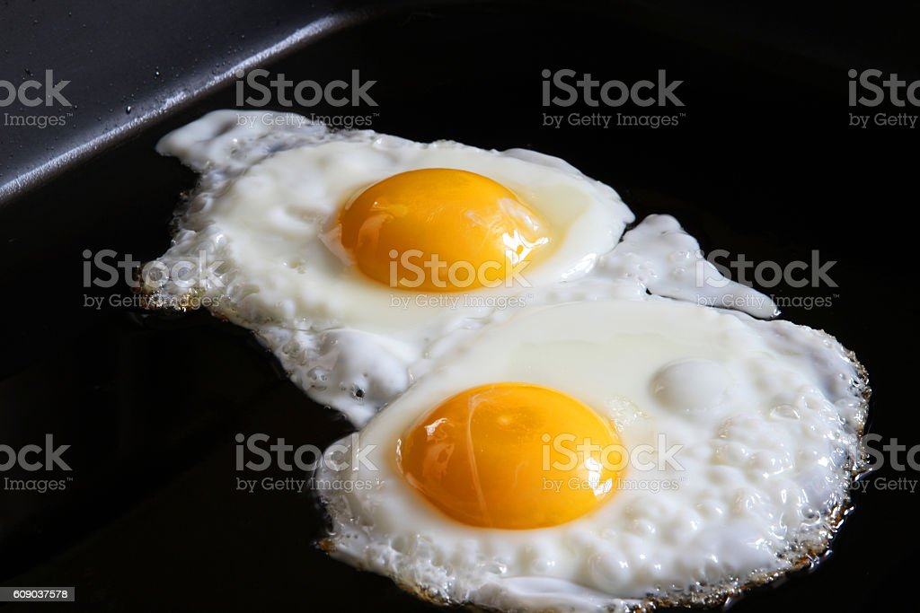 eggs sunny side up on frying pan closeup stock photo