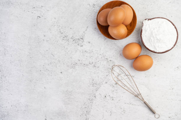 Eggs, tapioca flour in a cup and beat eggs on a white cement floor. stock photo