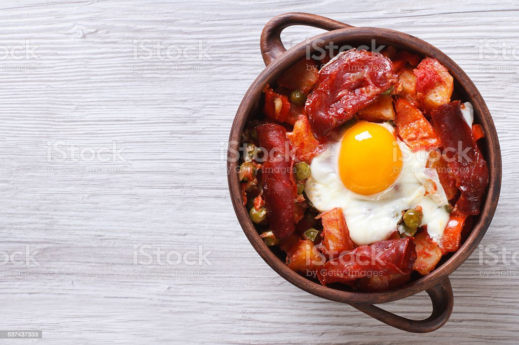 eggs with chorizo, potatoes and tomatoes in pot. top view stock photo