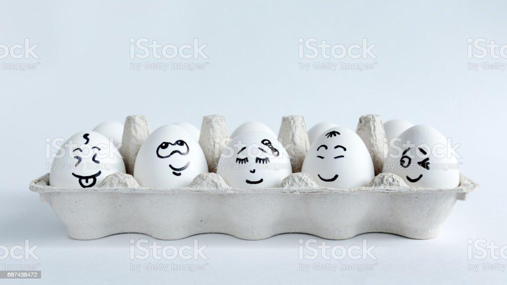 Eieren met grappige gezichten in het pakket op een witte achtergrond. Pasen Concept foto. Gezichten op de eieren - Royalty-free Ei Stockfoto