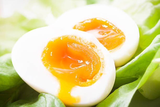 Eggs with runny yolk on a lettuce bed stock photo