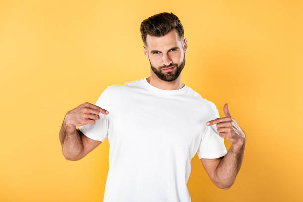 egotistical handsome man in white t-shirt pointing with fingers at himself isolated on yellow egotistical handsome man in white t-shirt pointing with fingers at himself isolated on yellow white t shirt stock pictures, royalty-free photos & images
