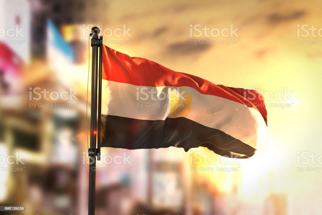 Bandera de Egipto contra ciudad borrosa de fondo en contraluz amanecer - foto de stock