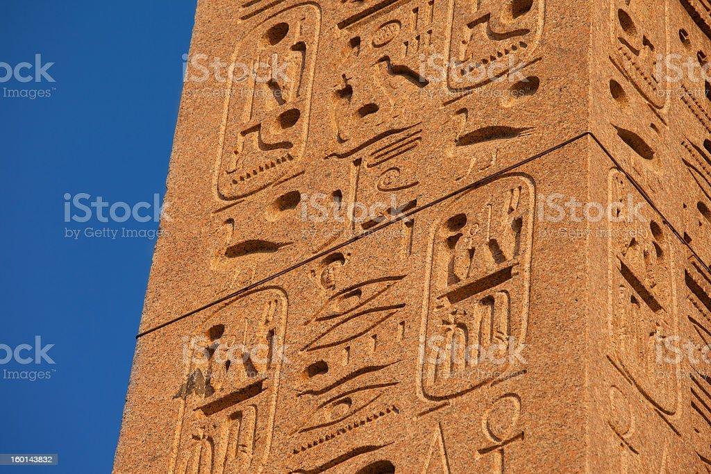 Egyptian hieroglhyps on ancient granite red column, blue sky stock photo