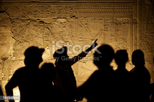 Egyptian hieroglyphs make an interesting background for silhouetted group of tourist archeologists