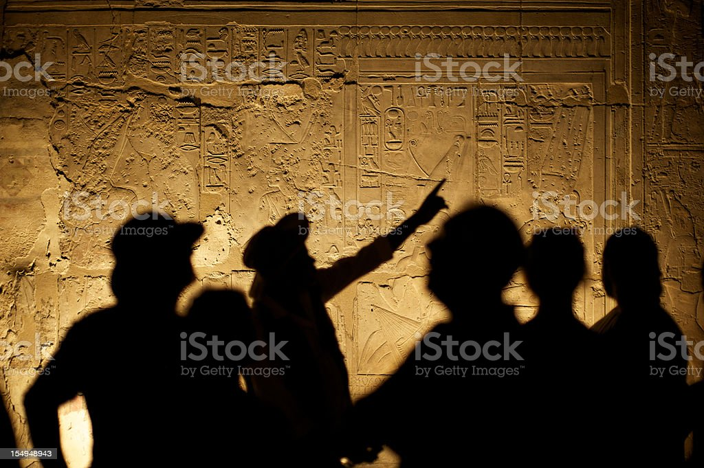 Egyptian Hieroglyphs with Tourist Archeologist Silhouettes stock photo