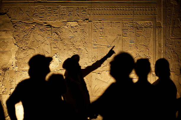 Egyptian Hieroglyphs with Tourist Archeologist Silhouettes Egyptian hieroglyphs make an interesting background for silhouetted group of tourist archeologists archaeology stock pictures, royalty-free photos & images