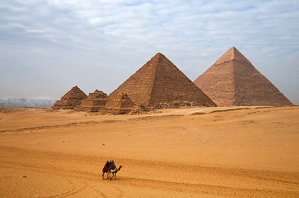 egyptian pyramid and the rider on the camel - pyramid stock photos and pictures