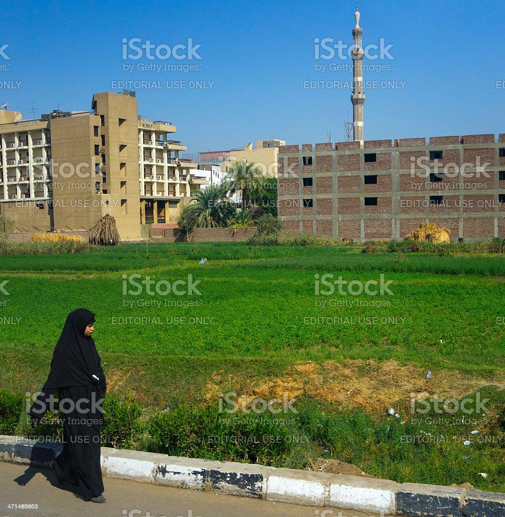 Egyptian woman in burkha Luxor, Egypt - October 31, 2012: a Muslim woman wearing a burkha is walking along a street. Adult Stock Photo