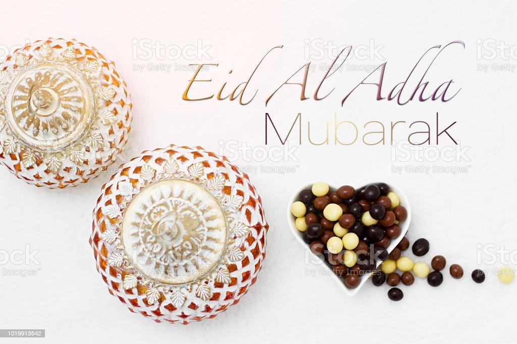 Eid Al Adha sacrifice festival, Islamic Arabic candle and sweet chocolate sugar. Eid al adha mubarak means happy festival of sacrifices stock photo