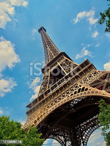 View up the iron structure of the Eiffel Tower in Paris. The sky above is blue, with only a few clouds as a frame.