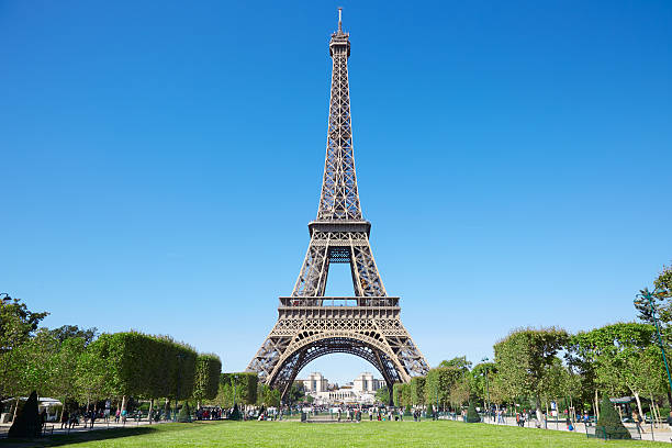 eiffel tower and green field of mars in paris - eiffel tower stock photos and pictures