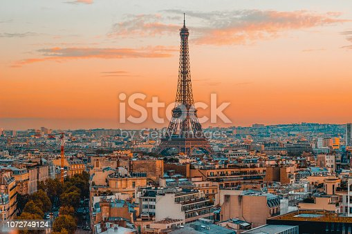 Breathtaking view of the Eiffel Tower and the serene Paris skyline during a vibrant European sunset, captured from the top of the Arc de Triomphe.