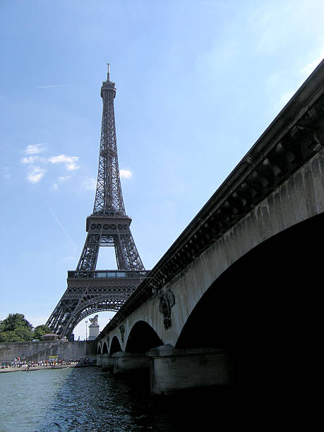 Eiffel Tower from riverbank Eiffel Tower with bridge in foreground. skeable stock pictures, royalty-free photos & images