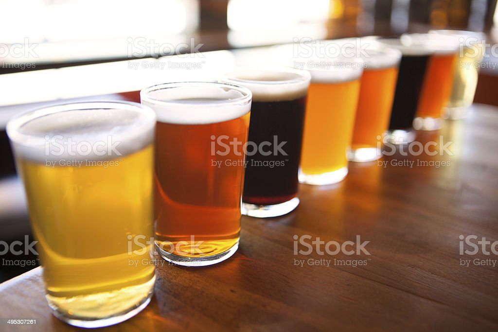 Eight beer samplers lined up on a table royalty-free stock photo