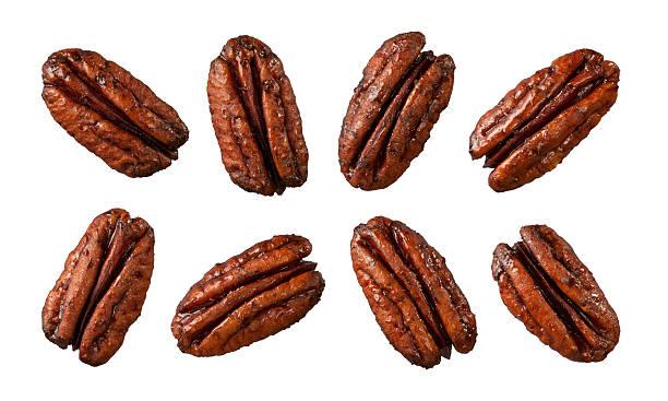 eight caramelized pecans isolated on white - geglazuurd stockfoto's en -beelden